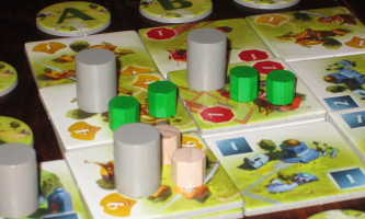 The gray cylinders mark the board so it's easy to tell at a glance the cards that need to be added to the deck when it's time to reshuffle.
